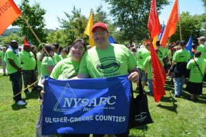 Two people in green shirts stand away from a crowd, holding a flag that says 'NYSARC inc, Ulster-Greene counties""