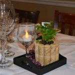 A centerpiece of a tea light in a wine glass, beside a plant in a small planter made of corks