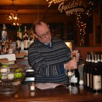 A man in a striped sweater standing behind a bar, opening a bottle of champagne