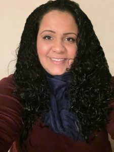 A smiling woman with curly dark hair and a blue scarf