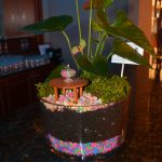 A fairy garden featuring a small table and brightly colored pebbles