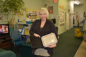a woman with short blonde hair holding a certificate