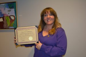 A woman in a purple shirt holding a certificate