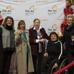5 women pose together, 3 of them holding glasses of wine and one of them using a wheelchair, smile together in front of a banner