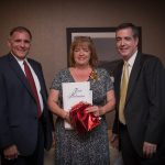 A woman in a patterned dress standing between two men in suits. She's holding a red gift bag and a certificate