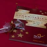A wrapped chocolate favor and a booklet that reads '36th annual humanitarian awards dinner' on a red tablecloth