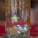 A glass jar centerpiece, with gold glitter and stars